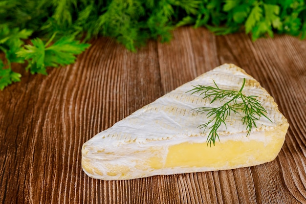 Slice of brie creme cheese on wooden surface