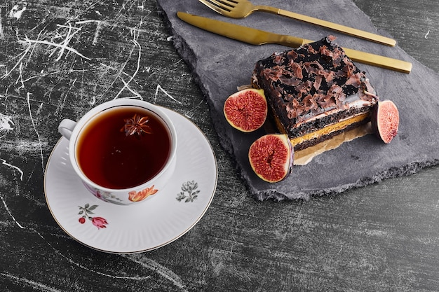 Una fetta di torta brownie con fichi e una tazza di tè.