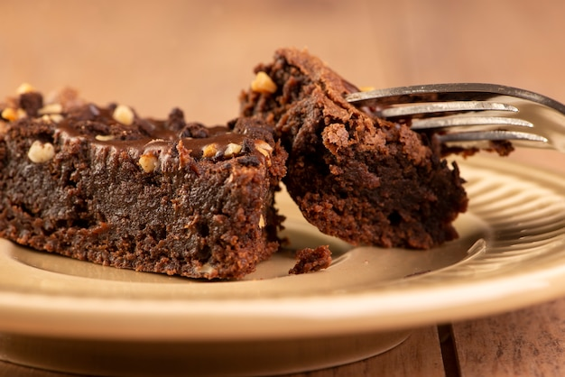 A slice of brownie on a plate on wooden table.