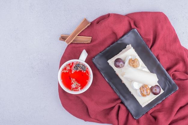 Una fetta di torta in un piatto di ceramica con una tazza di tisana rossa.