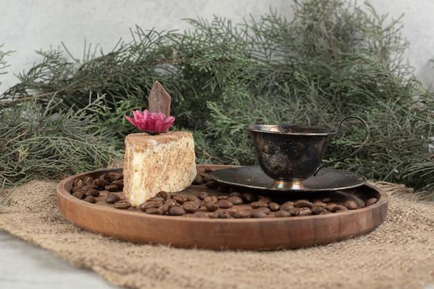 Fetta di torta, caffè e chicchi di caffè sul piatto di legno