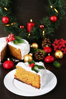 Slice of cake covered cream with christmas decoration on wooden table