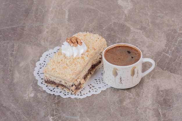 Slice of cake and cup of coffee on marble surface.