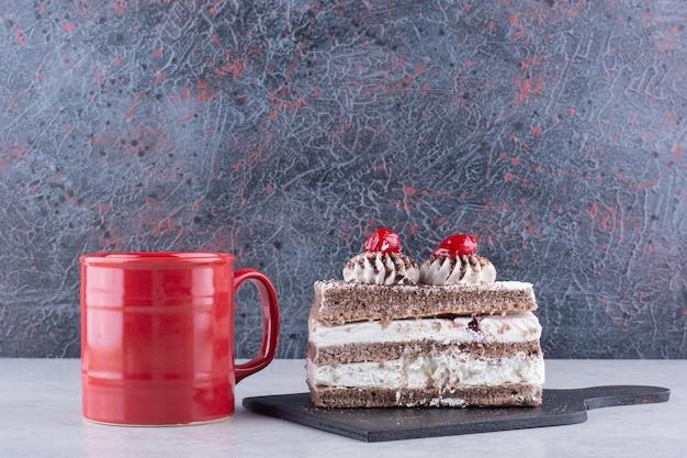 Fetta di torta sul bordo scuro con una tazza di tè sul tavolo di marmo. foto di alta qualità