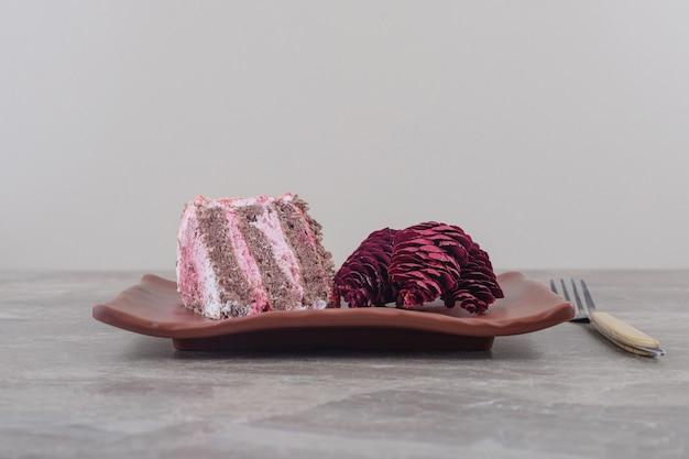 Una fetta di torta e pigne rosse su un vassoio accanto a una forchetta su marmo
