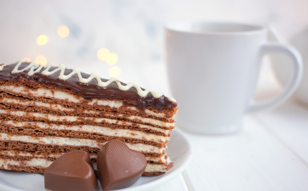 Slice of cake on a saucer and hearts on a white background