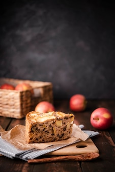Slice of cake with apples and wooden spoon