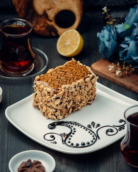 A slice of cake with caramel sauce decoration and peanuts.