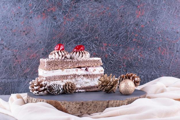 Fetta di torta con ornamenti natalizi su un pezzo di legno. foto di alta qualità