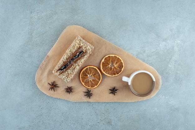 Fetta di torta con fette d'arancia e caffè su tavola di legno. foto di alta qualità