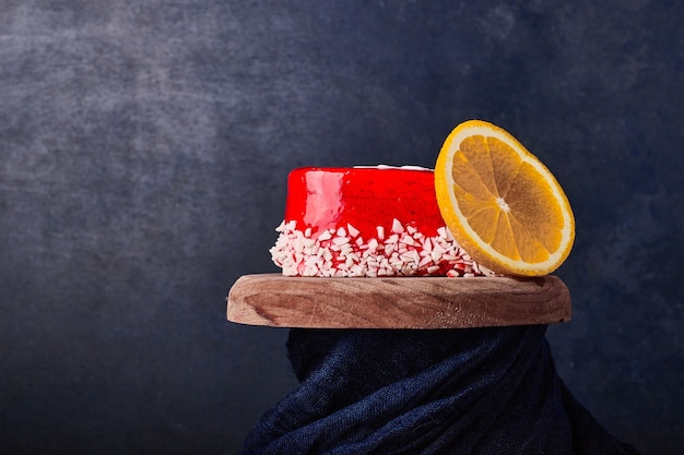 A slice of cake with red syrup and fruit.