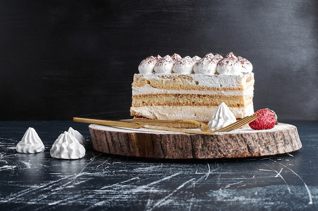 A slice of cake on a wooden board.