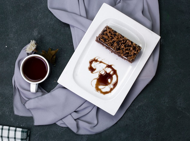 A slice of caramel cake with chopped chocolate in white plate.