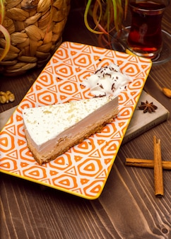Slice of caramel vanilla cheesecake on plate against a rustic brown wood table
