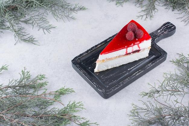 Fetta di cheesecake su tavola nera con ramo di pino. foto di alta qualità