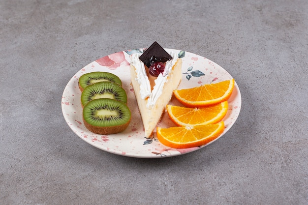 Slice of cheesecake on plate with fruits