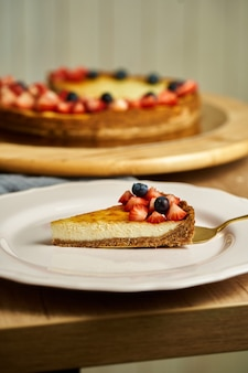 Slice of cheesecake on plate. wooden background