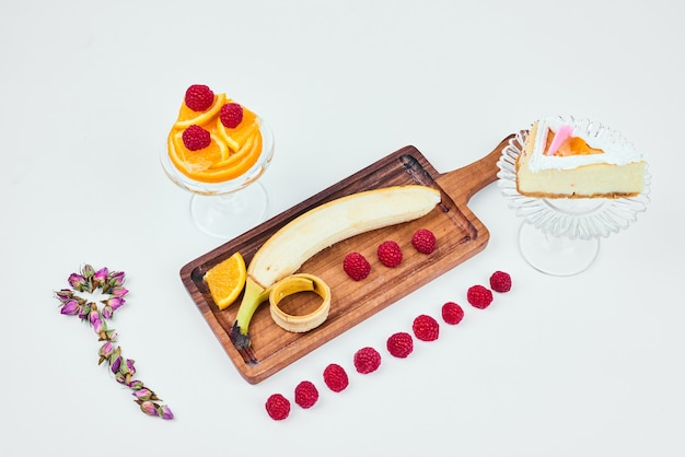 A slice of cheesecake with a fruit platter aside.