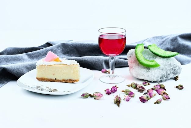 Una fetta di cheesecake con un bicchiere di bevanda.