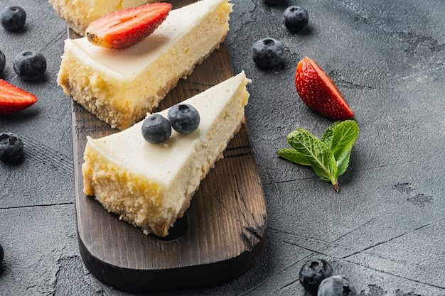 Slice of cheesecake with strawberries, blueberry, and mint, on gray table