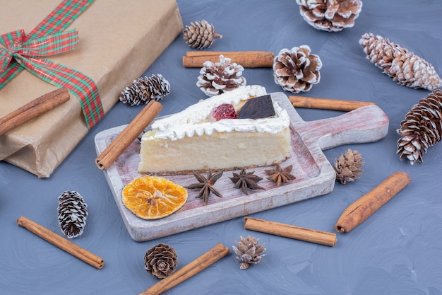 A slice of cheesecake in a wooden platter with anise flowers and cinnamon sticks