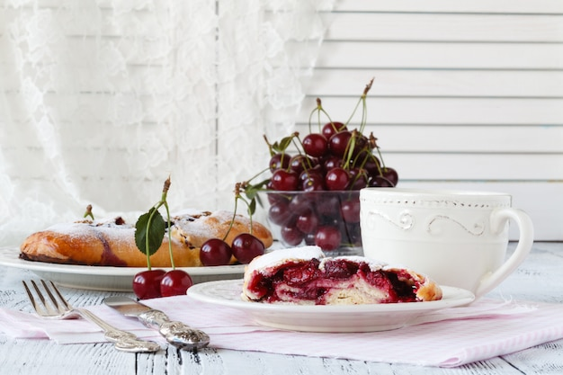 Slice of cherry pie with ice cream on a white textile background