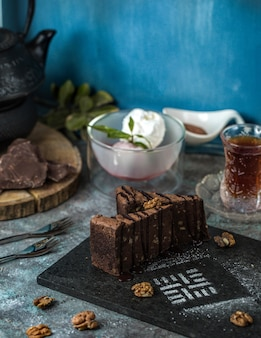 A slice of chocolate brownie cake with a glass of tea