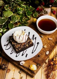 A slice of chocolate brownie with walnut and vanilla ice cream.