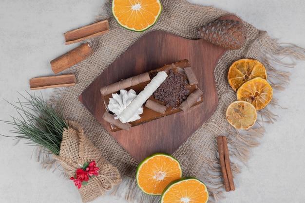 Slice of chocolate cake, cinnamon and slices of tangerine on burlap. high quality photo