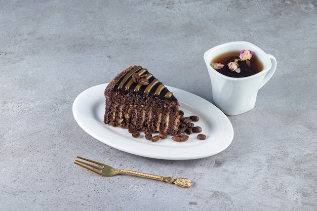 Slice of chocolate cake and glass of tea on stone table.