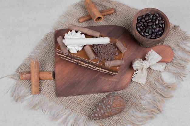 Fetta di torta al cioccolato, cereali e cinnamons su tela da imballaggio.