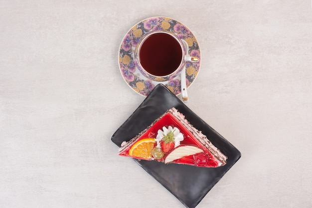 Slice of chocolate cake on plate with fruit slices and cup of tea.