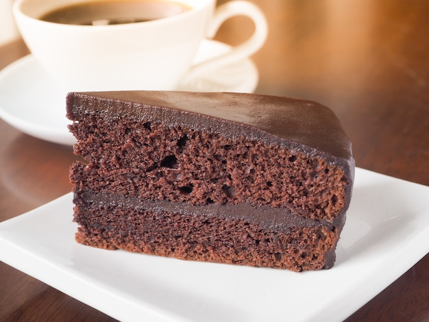 Slice of chocolate cake on a white plate. chose up of chocolate layer cake.