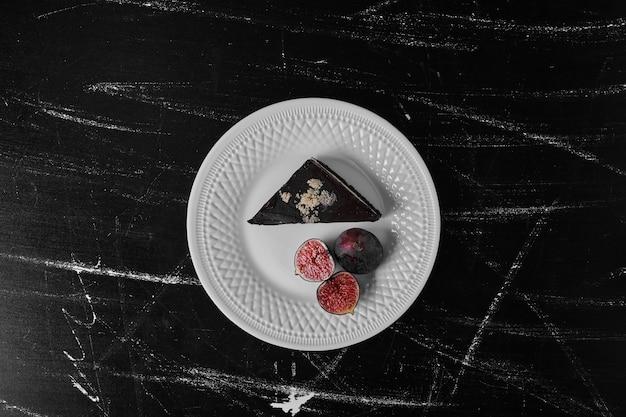 Una fetta di torta al cioccolato in un piatto bianco con i fichi da parte.