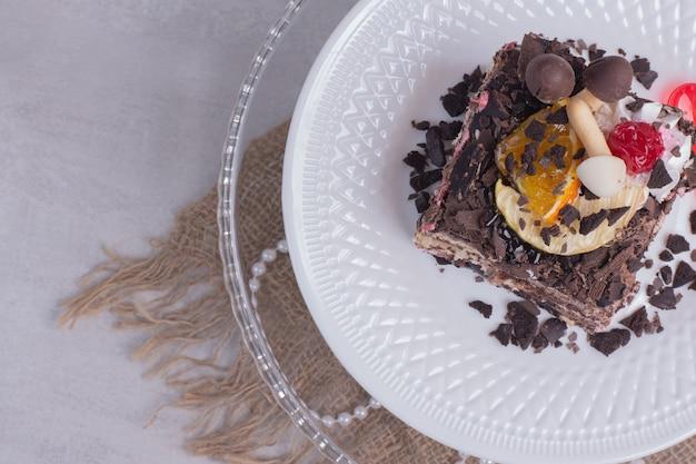 Fetta di torta al cioccolato sulla zolla bianca con perle.