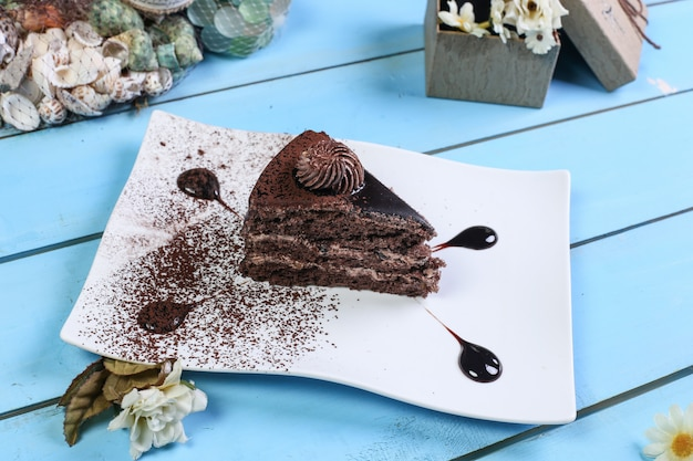 A slice of chocolate cake with cocoa powder.