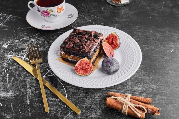 Una fetta di torta al cioccolato con fichi e tè in un piatto bianco.