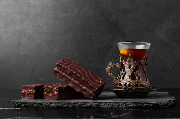 A slice of chocolate cake with a glass of tea.
