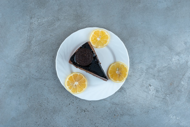 Slice of chocolate cake with lemon slices on white plate. high quality photo