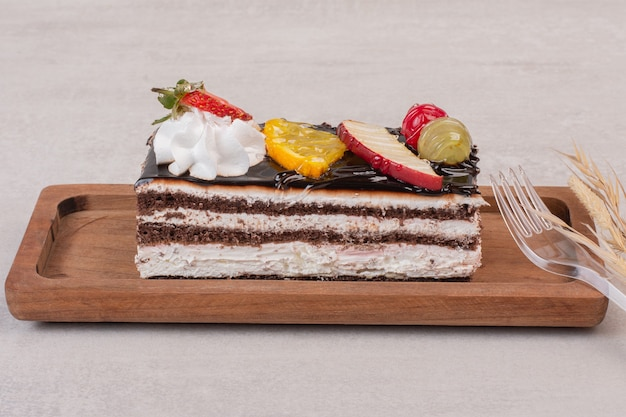 Slice of chocolate cake on wooden board with fruit slices.