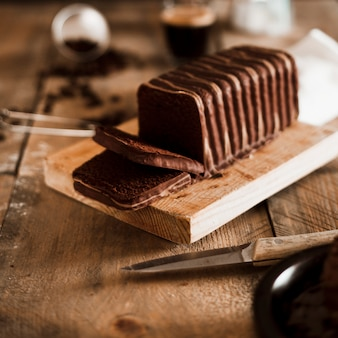 Slice of chocolate cake on wooden board with sharp knife