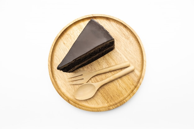 Slice of chocolate cake on the wooden plate isolate white background