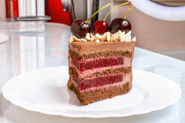 Slice chocolate caramel cake with cherries on white plate