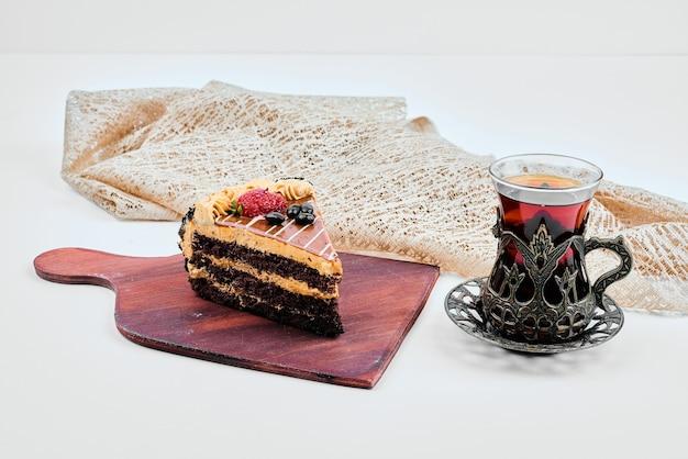 Una fetta di torta al cioccolato e caramello con un bicchiere di tè.