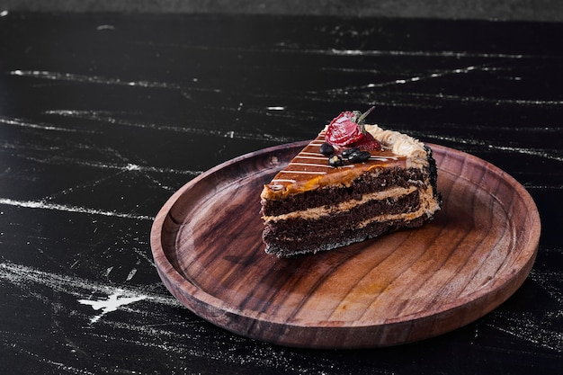 A slice of chocolate caramel cake in a wooden plate.