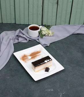 A slice of chocolate cheesecake and a cup of tea