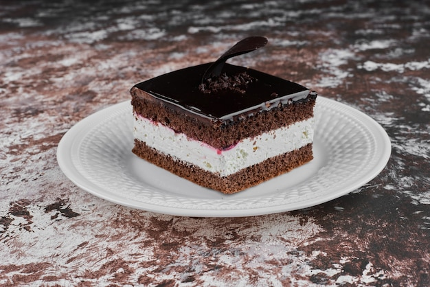 A slice of chocolate cheesecake in a white plate.