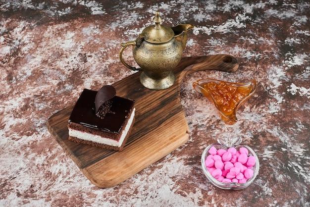 Una fetta di cheesecake al cioccolato con confettura e caramelle.