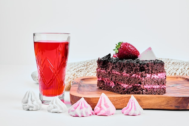 A slice of chocolate cheesecake with a glass of drink.