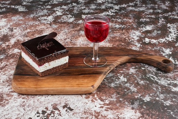 A slice of chocolate cheesecake with a glass of wine.